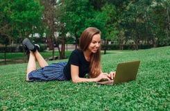 研究膝上型计算机的女孩说谎在草 免版税图库摄影