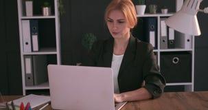 研究膝上型计算机的女实业家在办公室 股票录像