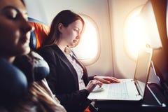 研究膝上型计算机的女性企业家坐在飞机的窗口附近 库存照片