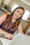 研究膝上型计算机的女性夫人在厨房里 免版税库存图片
