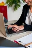 研究膝上型计算机的女性经理的播种的图象 免版税库存图片