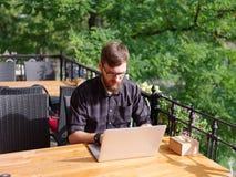 研究膝上型计算机的好年轻人,当坐户外时 到达天空的企业概念金黄回归键所有权 免版税图库摄影