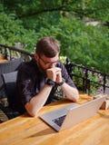 研究膝上型计算机的好年轻人,当坐户外时 到达天空的企业概念金黄回归键所有权 库存图片