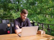 研究膝上型计算机的好年轻人,当坐户外时 到达天空的企业概念金黄回归键所有权 免版税库存图片