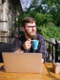 研究膝上型计算机的好年轻人,当坐户外时 到达天空的企业概念金黄回归键所有权 免版税库存照片