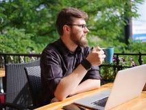 研究膝上型计算机的好年轻人,当坐户外时 到达天空的企业概念金黄回归键所有权 库存照片