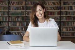 研究膝上型计算机的妇女企业家在共同工作的办公室或图书馆,对照相机的神色,微笑,书架 知识 免版税库存图片
