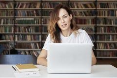 研究膝上型计算机的妇女企业家在共同工作的办公室或图书馆,对照相机的神色,聪明,书架 知识 库存图片