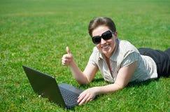 研究膝上型计算机的妇女在室外的夏天,在您的腹部的谎言在绿草草甸,显示最佳的姿态,愉快的人民,城市公园 图库摄影