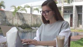 研究膝上型计算机的妇女在热带豪华别墅的水池附近 在计算机上的女性工作 在线商业 热的巧克力 免版税库存照片