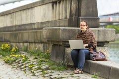 研究膝上型计算机的妇女,当坐一个石堤防时 自由职业者 图库摄影