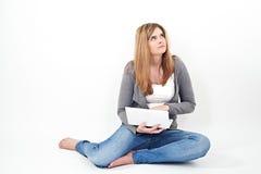 研究膝上型计算机的妇女,当坐地板时 免版税库存照片