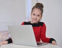 研究膝上型计算机的小女孩坐在桌上 免版税库存照片