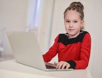 研究膝上型计算机的小女孩坐在桌上 图库摄影
