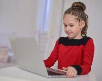 研究膝上型计算机的小女孩坐在桌上 库存图片