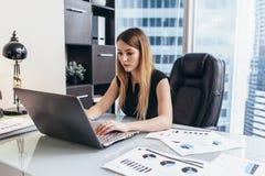 研究膝上型计算机的少妇学习公司的财务数据和统计 免版税库存图片
