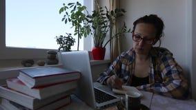 研究膝上型计算机的少妇,当在家时坐 股票录像
