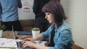 研究膝上型计算机的年轻人满意对被完成的工作 股票录像