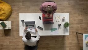 研究膝上型计算机的年轻人,给文件同事, topshot,坐在桌上在现代办公室,工作概念 股票录像