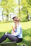 研究膝上型计算机的年轻俏丽的女孩室外,说谎在草,白种人20岁 免版税图库摄影