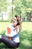 研究膝上型计算机的年轻俏丽的女孩室外,说谎在草,白种人20岁 库存图片