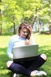 研究膝上型计算机的年轻俏丽的女孩室外,说谎在草,白种人20岁 免版税库存图片
