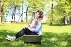 研究膝上型计算机的年轻俏丽的女孩室外,说谎在草,白种人21岁 库存图片