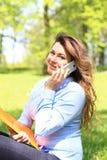 研究膝上型计算机的年轻俏丽的女孩室外,说谎在草,白种人21岁 免版税库存照片