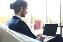 研究膝上型计算机的年轻商人,坐在等待某人的旅馆大厅 库存照片