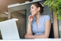 研究膝上型计算机的年轻女商人在办公室 库存图片