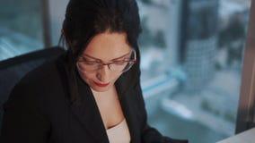研究膝上型计算机的年轻女实业家,当由窗口坐摩天大楼的一个高地板时 股票录像