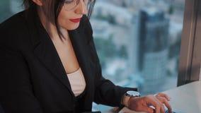 研究膝上型计算机的年轻女实业家,当由窗口坐摩天大楼的一个高地板时 影视素材