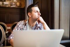 研究膝上型计算机的年轻成功的商人,当坐在咖啡馆在工休午餐,周道企业家连接期间时 免版税库存照片