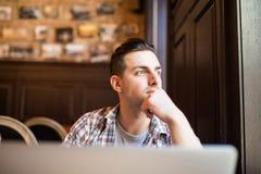 研究膝上型计算机的年轻成功的商人,当坐在咖啡馆在工休午餐,周道企业家连接期间时 图库摄影