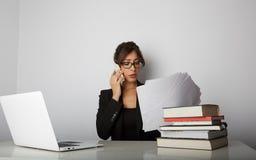 研究膝上型计算机的年轻白种人美丽的妇女坐在现代房子空的白色背景的桌上  免版税库存图片
