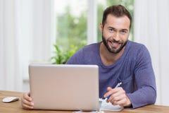 研究膝上型计算机的微笑的商人 免版税库存照片