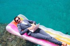 研究膝上型计算机的微笑的女实业家在海边 免版税库存照片