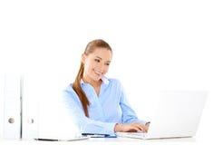 研究膝上型计算机的微笑的女实业家 免版税库存图片
