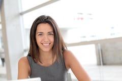 研究膝上型计算机的微笑的学生 免版税库存图片