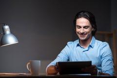 研究膝上型计算机的微笑的宜人的杨人 免版税库存照片
