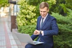 研究膝上型计算机的微笑的年轻人,当坐户外时 到达天空的企业概念金黄回归键所有权 免版税库存照片