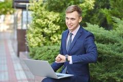 研究膝上型计算机的微笑的年轻人,当坐户外时 到达天空的企业概念金黄回归键所有权 免版税图库摄影