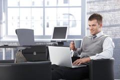 研究膝上型计算机的微笑的生意人在办公室 免版税库存照片