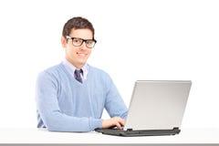研究膝上型计算机的微笑的男 图库摄影