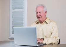 研究膝上型计算机的微笑的老人 库存图片