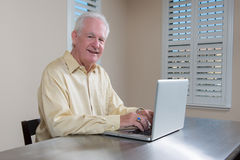研究膝上型计算机的微笑的老人 免版税库存照片