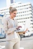 研究膝上型计算机的快乐的典雅的女实业家 免版税库存图片