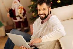 研究膝上型计算机的愉快的人在圣诞节期间 免版税库存图片