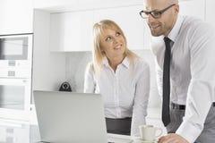 研究膝上型计算机的愉快的企业夫妇在厨房里 免版税库存照片