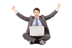 研究膝上型计算机的愉快的商人 免版税图库摄影